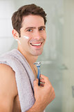 Smiling handsome man shaving in bathroom
