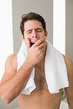 Shirtless man yawning with eyes closed at home