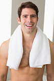 Shirtless man with towel around neck at home