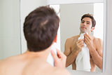 Young man looking at self in bathroom mirror