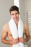 Shirtless young man with towel around neck