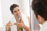 Man with reflection putting moisturizer on his face