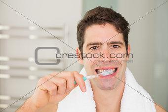 Close up portrait of man brushing teeth in bathroom