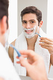 Young man with reflection shaving in bathroom