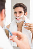 Handsome young man with reflection shaving in bathroom
