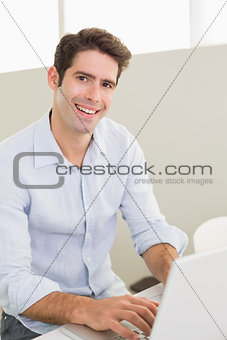 Portrait of casual smiling man using laptop at home