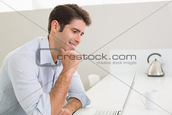 Casual young man using laptop at home