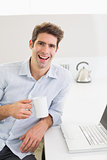 Cheerful casual man with coffee cup with laptop at home
