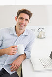 Smiling casual man with coffee cup with laptop at home