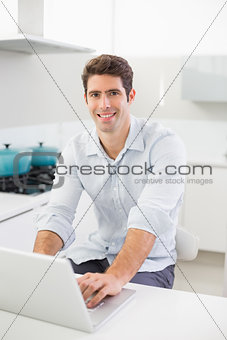 Smiling casual young man using laptop in kitchen