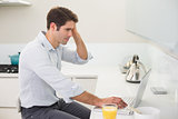 Concentrated casual man using laptop in kitchen