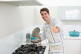 Smiling young man gesturing thumbs up in kitchen
