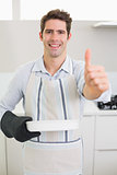 Man with baking dish gesturing thumbs up in kitchen
