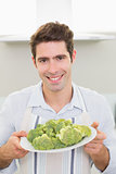 Smiling man holding a plate of broccoli in kitchen