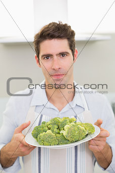 Handsome man holding a plate of broccoli in kitchen