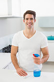 Smiling young man cleaning kitchen counter
