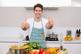 Smiling man with vegetables gesturing thumbs up in kitchen