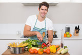 Smiling young man chopping vegetables in kitchen