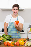 Smiling man holding bell pepper with vegetables in kitchen