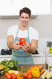 Smiling man holding out bell pepper with vegetables in kitchen