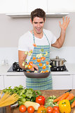 Cheerful man tossing vegetables in kitchen