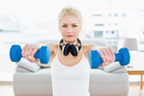 Fit woman with dumbbells at fitness studio