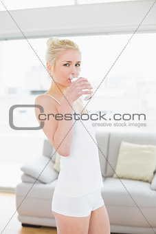 Portrait of fit young woman drinking water at the gym