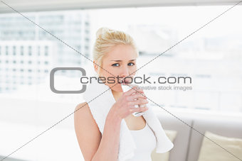 Fit young woman drinking water at the gym