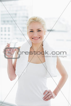 Fit smiling woman with a glass of water at gym