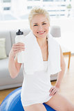 Smiling woman with water bottle sitting on exercise ball