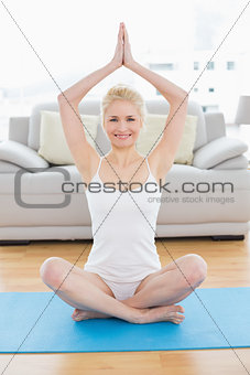 Toned woman with joined hands over head at fitness studio