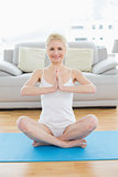 Toned woman sitting in Namaste position at fitness studio