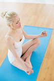 Toned woman sitting in lotus pose at fitness studio