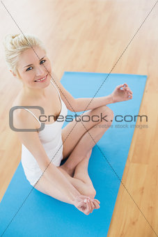 Portrait of toned woman in lotus pose at fitness studio