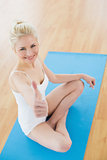 Toned woman gesturing thumbs up on exercise mat at fitness studio
