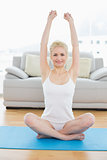 Smiling sporty woman stretching hands upward in fitness studio