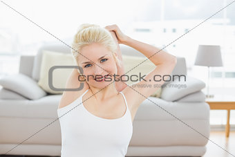 Toned woman stretching hands behind head in fitness studio