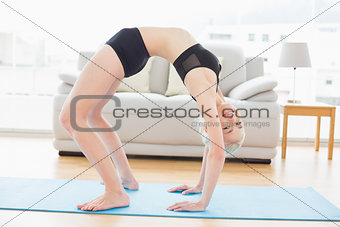 Fit woman doing the wheel pose in fitness studio