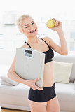 Fit woman in sportswear holding scale and apple in fitness studio