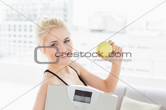 Fit woman holding scale and apple in fitness studio