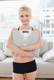Woman in sportswear carrying scale in fitness studio