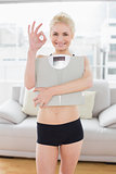 Woman carrying scale while gesturing okay sign