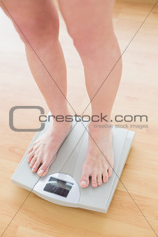 Close up of woman standing on weighing scale