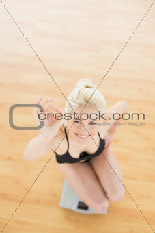 Cheerful woman gesturing ok sign on scale in fitness studio
