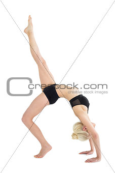 Fit woman doing the wheel pose with one leg raised