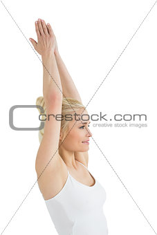 Toned young woman with joined hands over head
