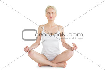 Toned young woman sitting in lotus pose with eyes closed