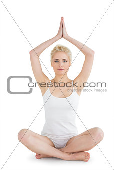 Toned young woman sitting with joined hands over head