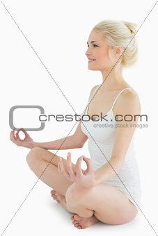 Toned young woman sitting in lotus position