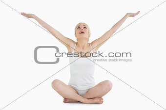 Toned young woman sitting with arms outstretched